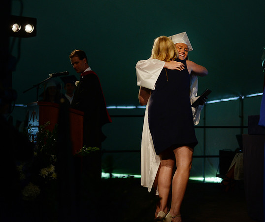 PAUL BILODEAU/Staff photo. Bethany Evans receives a hug from her mother, School Committee member, Deb Evans, during Hamilton-Wenham Regional High School's graduation ceremony in a tent on the football field at the school.