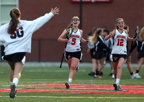 DAVID LE/Staff photo. Marblehead juniors Lucie Poulin (5) and Amanda Gregory (12) streak downfield towards a teammate after the Magicians captured the D2 North Title over Ipswich. 6/9/16.
