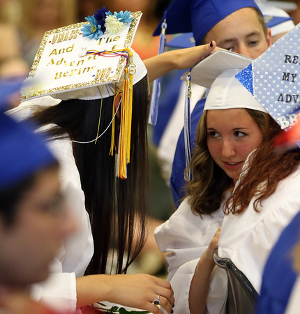DAVID LE/Staff photo. Danvers High School graduate McKenzie Plaza, left, helps classmate Olivia O'Keefe, right, re-attach her tassel to her mortar board during graduation on Saturday afternoon. 6/11/16.