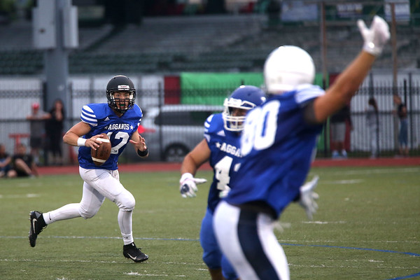 HADLEY GREEN/ Staff photo<br /> North's Drew Gally (12) of Marblehead looks to pass the ball while Jake Doherty (80) of Peabody gets open at the Agganis boys football all-star game at the Manning Field in Lynn. 6/28/17