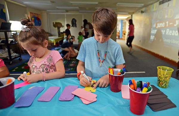 RYAN HUTTON/ Staff photo<br /> Jack Siniscalchi, 7, and his sister Veronica, 5, color their own bookmarks at the Salem Public Library's kid's summer reading program kick off party on Wednesday.