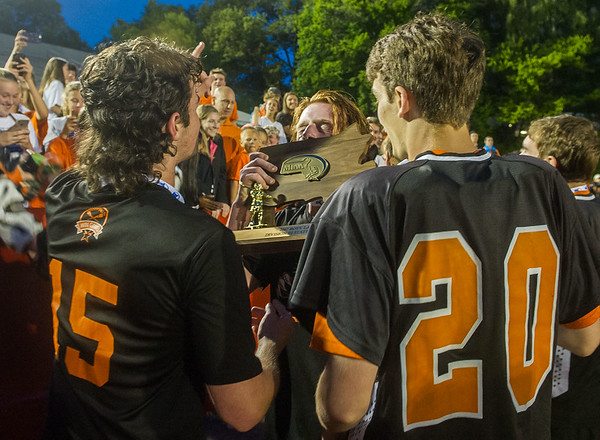 Ipswich's Charlie Gillis (17) kisses the MIAA trophy as the team celebrates their win.