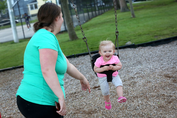 HADLEY GREEN/ Staff photo<br /> Lauren Gill of Danvers pushes her daughter Brielle Gill on the swings at the playground next to the Twi Field in Danvers. 6/01/17