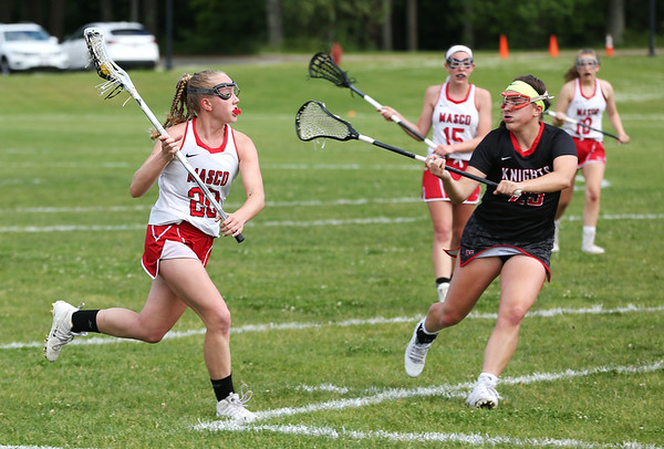 Staff photo/ HADLEY GREEN<br /> Masconomet's Nicole Amyouny (20) runs with the ball while North Andover's Kelly Corrigan (25) plays defense.<br /> <br /> 06/05/2018