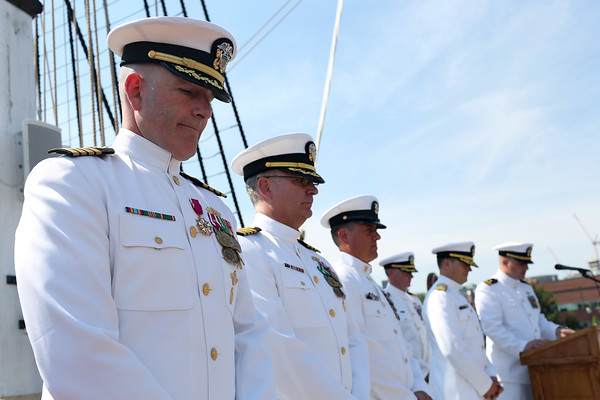 Staff photo/ HADLEY GREEN<br /> Salem native Capt. Stephen Cook, left, stands during the benediction at his retirement ceremony from the U.S. Navy on the USS Constitution. <br /> <br /> 06/29/2018