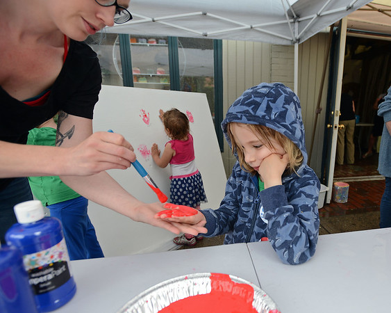 RYAN HUTTON/ Staff photo<br /> Tia Cole paints the hand of Cuillin Swan-Grimes, 4, to add to the Rise Your Hands Up! wall behind them at the Salem Farmer's Market on Thursday. The wall is meant to draw attention to the plight of migrant children being separated from their parents at the US-Mexican border.