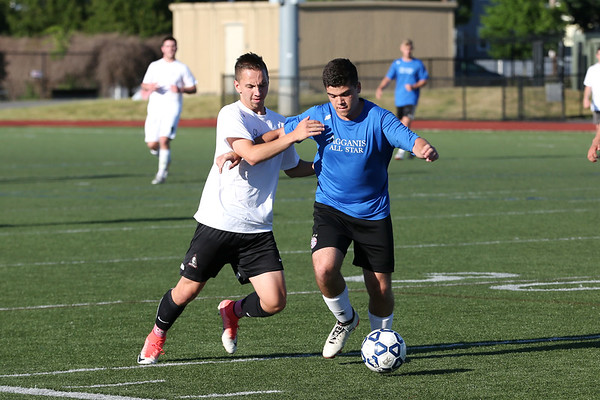 Staff photo/ HADLEY GREEN<br /> South's Chris Belliveau (1) of Peabody and North's Matthew Riccardi (12) of Lynnfield vie for the ball at the Agganis boys soccer all-star game.<br /> <br /> 06/26/2018
