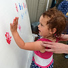 RYAN HUTTON/ Staff photo<br /> Scarlet Theriault, 3, adds her hand print to the Raise Up Your Hands! wall at the Salem Farmer's Market on Thursday. The wall is meant to draw attention to the plight of migrant children being separated from their parents at the US-Mexican border.