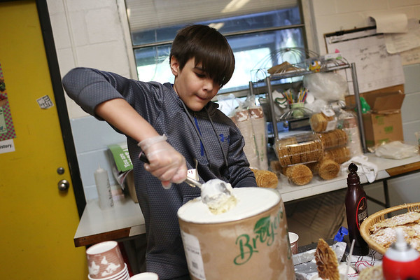 Staff photo/ HADLEY GREEN<br /> Sixth grader Nayle Qureshi scoops ice cream for the dessert course at Swampscott Middle School's charity dinner to support Feeding America. The ice cream was provided by Castle Creek Adventure Land. <br /> <br /> 06/12/2018