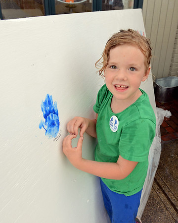 RYAN HUTTON/ Staff photo<br /> Serenity Theriault, 5, poses next to her hand print on the Raise Your Hands Up! wall at the Salem Farmer's Market on Thursday. The wall is meant to draw attention to the plight of migrant children being separated from their parents at the US-Mexican border.
