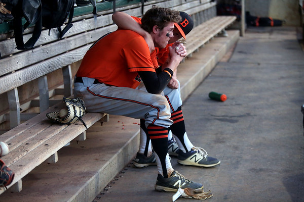 Staff photo/ HADLEY GREEN<br /> Beverly's Ryan Munzing (9) is comforted by a teammate after he gets out at first in the seventh inning during the team's contest against North Attleborough at LeLacheur Park in Lowell.<br /> <br /> 06/21/2018