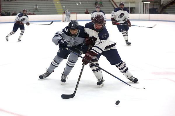 HADLEY GREEN/ Staff photo <br /> St. John's Paul Edson (2) and Belmont's Ben Brody (2) go after the puck at the St. John's Prep v. Belmont High Division 1 North MIAA playoff game at the Chelmsford Forum on Wednesday, March 1st, 2017.