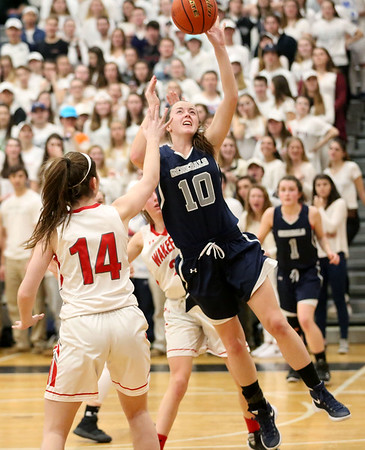 HADLEY GREEN/ Staff photo <br /> Hamilton-Wenham's Kelly Walsh (10) shoots while Wakefield's Julia Hanley (14) plays defense during the Hamilton-Wenham v. Wakefield Division 2 North quarterfinal girls basketball game at Woburn High School on Wednesday, March 8th, 2017.