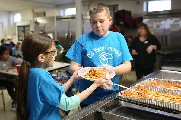 HADLEY GREEN/ Staff photo<br /> Jacob Richards, 12, passes a plate of pasta to Natasha Bhatia, 9, to serve at Haven from Hunger, a hunger-relief organization, in Peabody with their C3 group. C3 is a community service group from the Community Covenant Church in Peabody.