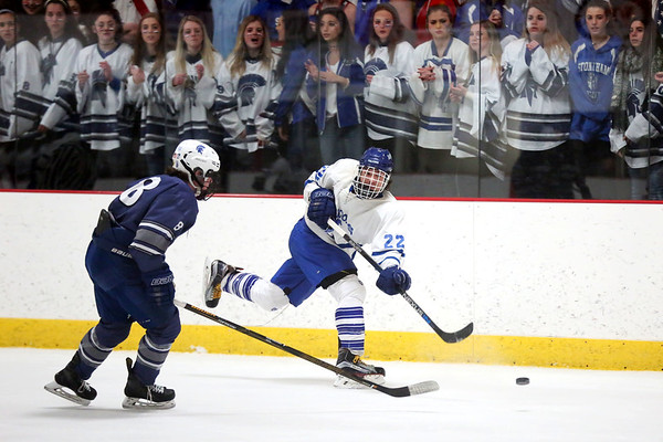 HADLEY GREEN/ Staff photo <br /> Danvers' Thomas Mento (22) shoots while Stoneham's Cam Sacco (8) plays defense at the Danvers v. Stoneham boys hockey playoff game at the O'Brien rink in Woburn on Friday, March 3rd, 2017.