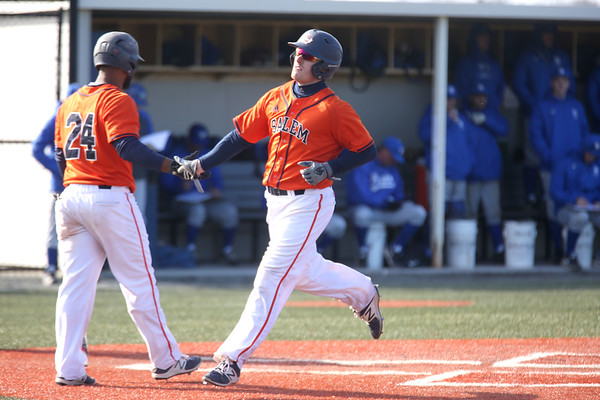 HADLEY GREEN/ Staff photo<br /> Salem State's Alex Toomey (17) high-fives his teammate as he runs through home plate at the Salem State v. Wheaton College men's varsity baseball at Salem State University on Thursday, March 30th, 2017.