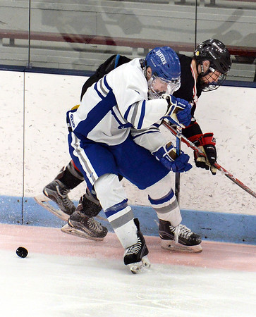 CARL RUSSO/Staff photo. Danvers' captain Conor Purtell and North Andover's captain Tyler Buonopane fight for the loose puck. North Andover defeated Danvers 5-2 in boys hockey in Division 2 North playoff quarterfinals. 3/01/2018