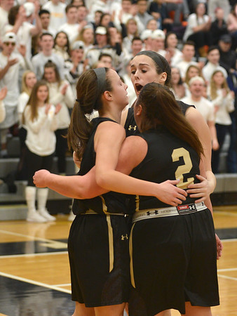 JIM VAIKNORAS/Staff photo Fenwick's Sammi Gallant is hugged by teammates #2 Fredi DeGuglielmo and Jenni Meagher against Archbishop Williams at Woburn high Wednesday night.