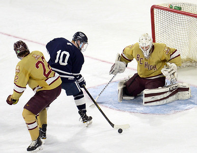 CARL RUSSO/staff photo St John's Zach McKennelley fights for the puck. St. John's Prep was defeated 1-0 by BC High in Super 8 hockey playoff action. 3/05/2018