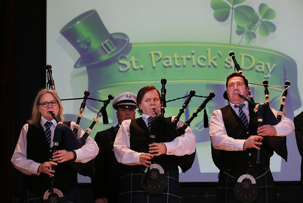 MIKE SPRINGER/Staff photo<br /> Members of the North Shore Pipe Band, from left, Liz Jones of Maynard, Nancy Sullivan of Ipswich and Dennis O'Brian of Georgetown play the bagpipes at the start of the annual St. Patrick's Day breakfast Saturday at Peabody City Hall.<br /> 3/17/2018