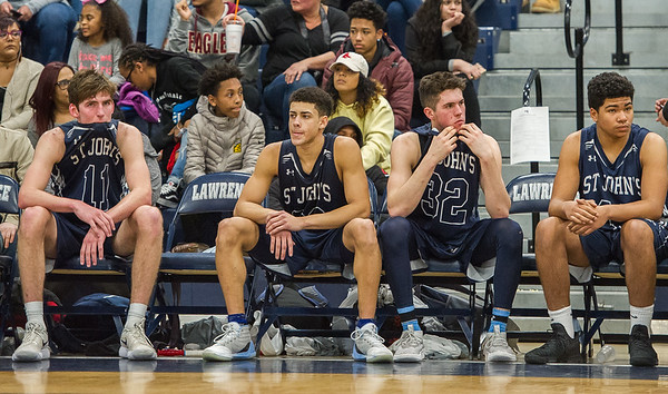 AMANDA SABGA/Staff photo<br /> <br /> St. John's Prep's players, from left, Tommy O'Neil, Nate Hobbs, Matt Relihan and Mason Davis react to their losing score during the D1 North quarterfinals at Lawrence High School. St. John's Prep fell 80-64 to Lawrence.<br /> <br /> <br /> 3/3/18