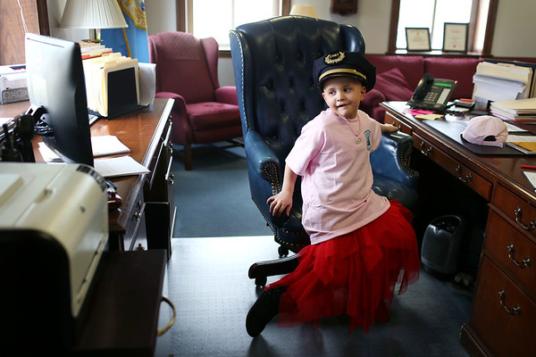 HADLEY GREEN/Staff photo<br /> After being sworn in as an honorary police officer, Dior Stavros, a 6-year-old girl from Salem who has leukemia, twirls in Salem Police Chief Mary Butler's desk chair while wearing her police chief hat. Dior's family was also given a donation from the organization Cops for Kids with Cancer. <br /> <br /> 03/09/18
