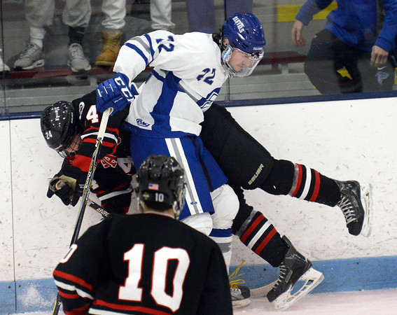 CARL RUSSO/Staff photo. Danvers' captain Thomas Mento checks North Andover's Mike Halloran into the boards. North Andover defeated Danvers 5-2 in boys hockey in Division 2 North playoff quarterfinals. 3/01/2018