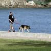 KEN YUSZKUS/Staff photo. Reginald Whitcomb, Jr., walks his dog Gunner on the seawall at Dane Street Beach late Tuesday afternoon.     5/26/15
