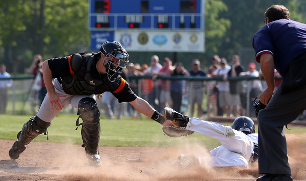 DAVID LE/Staff photo. Beverly junior catcher manages to swipe a tag on the leg of Danvers junior Max Paul as he slides past, trying to tag the plate ahead of the throw on a squeeze play. 5/27/16.
