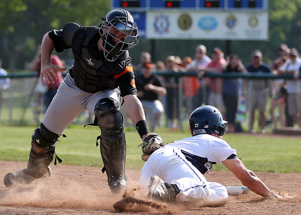 DAVID LE/Staff photo. Beverly junior catcher Luke Samperi reaches over and tags Danvers junior Max Paul as he tries to slide headfirst and beat the throw home on a squeeze play. 5/27/16.