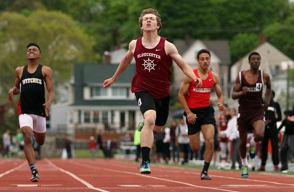 DAVID LE/Staff photo. Gloucester senior Jebediah Hogan lunges across the finish line in 23.33 seconds to capture the Boys 200 Meter dash after out-kicking the rest of the field down the straightaway. 5/21/16.