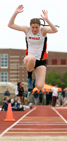 DAVID LE/Staff photo. Beverly junior Natalie Coughlin leaps high in the air and towards the pit as she completes one of her triple jumps at the NEC Conference Meet. 5/21/16.