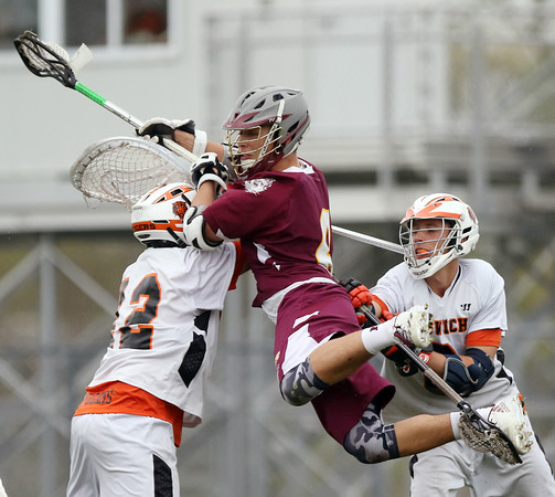 DAVID LE/Staff photo. Newburyport senior captain Will Fogel, center, gets checked in midair after firing off a shot by Ipswich goalie Aidan McAdams (12) and midfielder Blake Emerson, right.5/13/16.