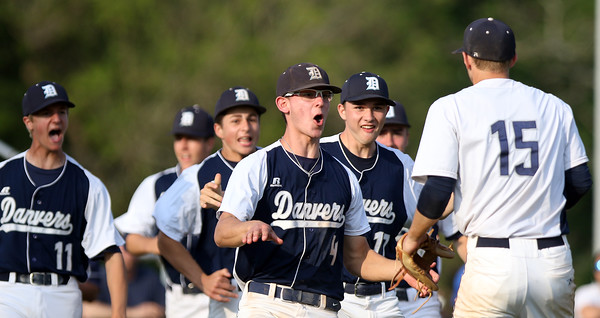 DAVID LE/Staff photo. Danvers junior Max Paul (4) is the first Falcon to reach senior captain Andrew Olszak (15) after he nailed down the save with a 1-2-3 7th inning to preserve a 4-3 Falcons win for the NEC title over Beverly. 5/27/16.