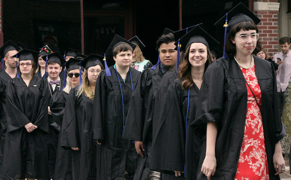 KEN YUSZKUS/Staff photo.    The Montserrat College of Art graduates cross Cabot Street and enter The Cabot at the start of their commencement ceremony.     05/13/16