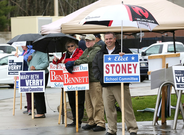 KEN YUSZKUS/Staff photo.    From left, Jan Pellegrini, selectman candidate Dan Bennett, and school committee candidate Richard Stoney along with others stand outside Danvers High School to greet voters on their way to vote.     05/03/16
