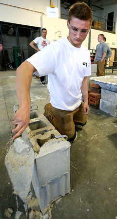 KEN YUSZKUS/Staff photo.       Essex Tech senior Joshua Fales, of Wenham, adds motar to his cement block wall that he is constructing during the annual Mass. Trowel Trades Association's competition held at Essex Tech.     05/11/16
