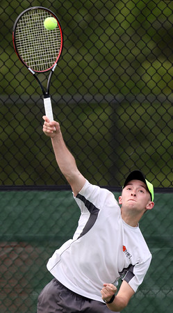 DAVID LE/Staff photo. Beverly senior and first doubles player Colin Oliver smashes a lofted return over the net against Marblehead. Oliver and Federico Poncini earned a win at first doubles to help the Panthers to a 3-2 win over the Magicians. 5/26/16.