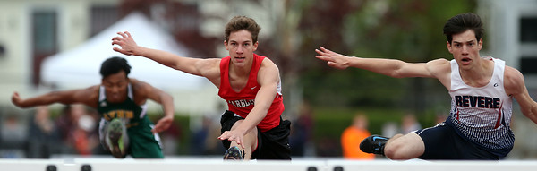 DAVID LE/Staff photo. Marblehead sophomore Thomas Huber, left, and Revere junior David Sinatra, right, leap neck-and-neck over the second to last high hurdle during the first preliminary heat. 5/21/16.