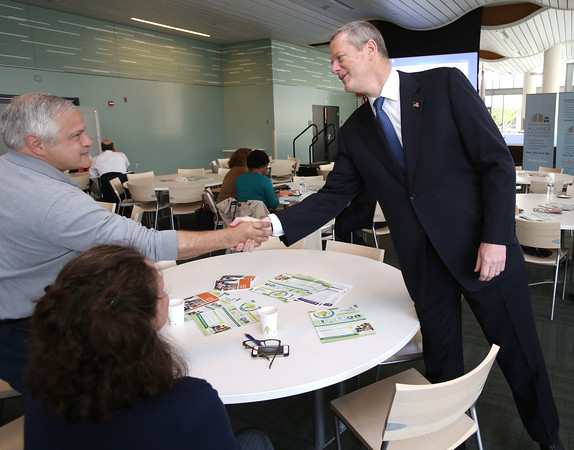 KEN YUSZKUS/Staff photo.     Gov. Charlie Baker, right, is greeted by Russell Robidoux of Mass Growth Capital when he arrived to speak to the North Shore Alliance for Economic Development at Salem State University Tuesday morning.     05/17/16