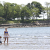 KEN YUSZKUS/Staff photo.    Kaye Mulvey and her son Jacoby, 2, of Beverly, walk in the shallow water at near low tide off Dane Street Beach.     05/31/16