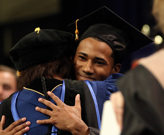DAVID LE/Staff photo. North Shore Community College graduate and Salem native Nathaniel Montero gets a big hug from NSCC President Dr. Patricia Gentile after he delivered a heartfelt Student Address on Thursday evening. 5/26/16.
