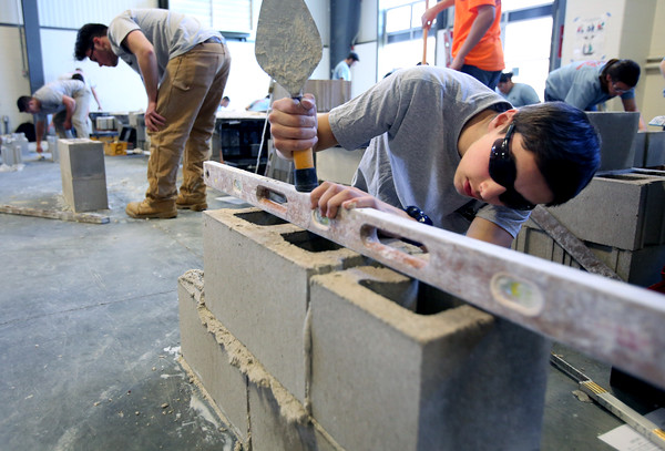 KEN YUSZKUS/Staff photo.       Essex Tech junior Scott Ogiba, right, of Beverly, uses a level to check his work while building a cement block wall during the annual Mass. Trowel Trades Association's competition held at Essex Tech. Fellow Essex Tech junior Sergio Aureli, left, of Topsfield, works on his wall.    05/11/16