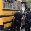 DAVID LE/Staff photo. Three interested kids stick their heads out the windows of their school bus as Salem Police officers examine damage done to the rear right tire and side of the bus after a collision on Thursday afternoon.5/5/16.
