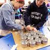 KEN YUSZKUS/Staff photo.    Hannah Elementary School fifth graders Katie Burgess and Jared Pieroni place the wicks into the containers that will eventually be filled with wax.     05/06/16