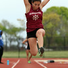 DAVID LE/Staff photo. Gloucester sophomore Kaitlin Marques leaps high in the air as she flies towards the sand pit while participating in the long jump at the NEC Conference Meet. 5/21/16.