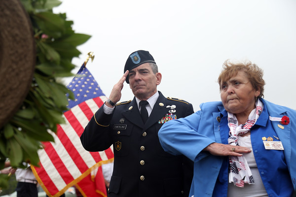 DAVID LE/Staff photo. Salem veterans agent Kim Emerling, left, and Vinnie Cavanaugh, right, salute after placing a wreath at a short ceremony at St. Mary's Cemetery in Salem on Sunday morning. 5/29/16.