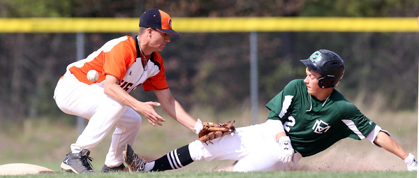 DAVID LE/Staff photo. The baseball skips away from Ipswich shortstop Liam Sullivan on a throw to second as Manchester-Essex shortstop Hunter Flood slides through his legs to reach the bag safely. 5/17/16.