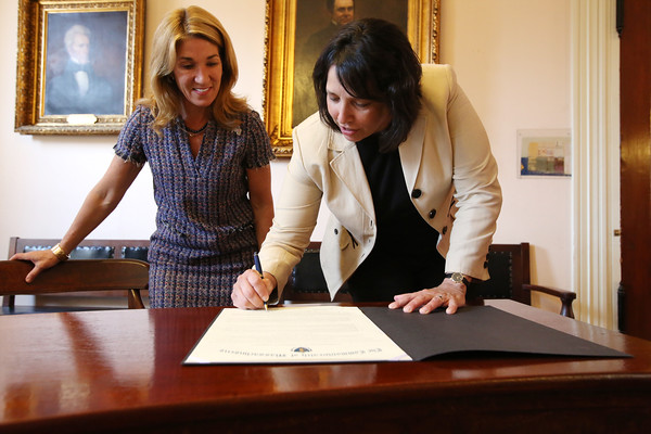 KEN YUSZKUS/Staff photo.          Lt. Gov. Karyn Polito, left, watches as Salem Mayor Kim Driscoll signs the community compact.           05/31/16