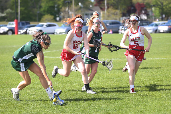 HADLEY GREEN/ Staff photo<br /> Manchester Essex's Carline Francouer (5) and Abby Lantz (7) run towards the ball while guarded by Masco's Tara Gallagher (12) and Joceyln Dalton (5) at the Masco v. Manchester Essex girls varsity lacrosse game held at Masconomet High School. 5/12/17
